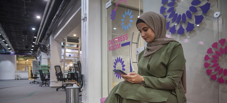 أماني علاونه، 22 عاما، تنتظر لقاء شريكها في العمل، اللاجئ السوري إيهاب قهواتي، في مجمع زين للإبداع بعمان.