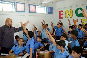Palestinian boys raise their hands during one of the first classes of the new academic year, at a school in Gaza supported by the United Nations Relief and Works Agency for Palestine Refugees in the Near East (UNRWA).