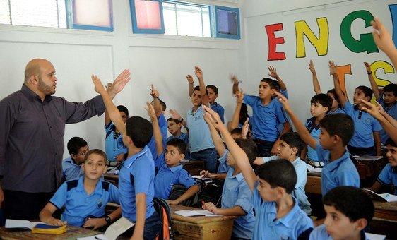 Niños palestinos alzan la mano durante una de las primeras clases del nuevo año académico, en una escuela de Gaza apoyada por la Agencia de las Naciones Unidas para los Refugiados Palestinos (UNWRA).