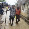 Two young men walk in the flooded Shibaburi area of Pemba after heavy rains poured down in the Pemba region of Mozambique (April 2019).