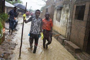 मोज़ांबीक के एक इलाक़े में भारी बारिश से आई बाढ़ में दो युवक - ये कुछ जलवायु परिवर्तन के चिन्ह हैं (अप्रैल 2019)