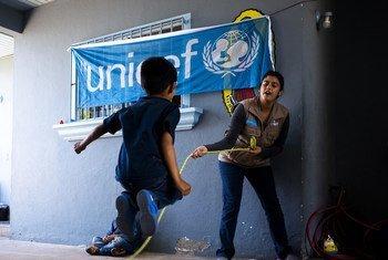 Un niño en un centro de Tijuana en México juega con una trabajadora de UNICEF.