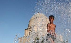 Un niño se refugia del calor en una fuente de la ciudad de Samarkand, Uzbekistán.