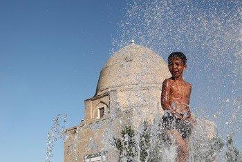 Menino de 11 anos no Uzbequistão refresca-se da onda de calor.