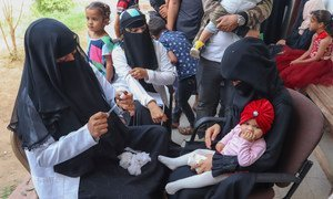 A health worker in Aden, Yemen, fills a needle as she prepares to vaccinate a young gild during a UNICEF-backed Measles and Rubella vaccination campaign in February 2019.