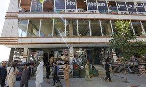Des commerçants à Kaboul, en Afghanistan, devant un bâtiment endommagé par l'attaque du 1er juillet 2019 revendiquée par les Talibans.