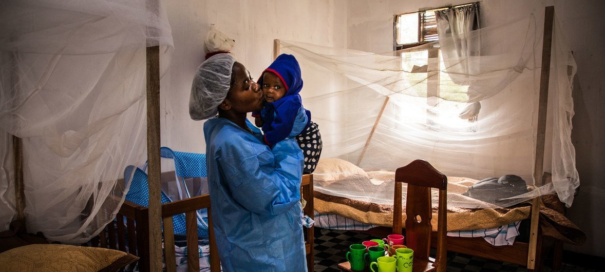 A caregiver at the Ebola Treatment Centre of Butembo, kisses a seven-month-old baby whose mother died of the Ebola just days earlier. North Kivu, Democratic Republic of Congo, 23 March 2019.