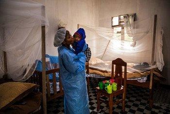 Um cuidador no Centro de Tratamento Ebola de Butembo, beija um bebê de sete meses que perdeu a mãe devido ao ebola poucos dias antes.