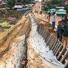 فرق الحد من أخطار الكوارث في برنامج الأغذية العالمي تعمل على تثبيت المنحدرات التي تراجعت أثناء هطول الأمطار الغزيرة في كوكس بازار.