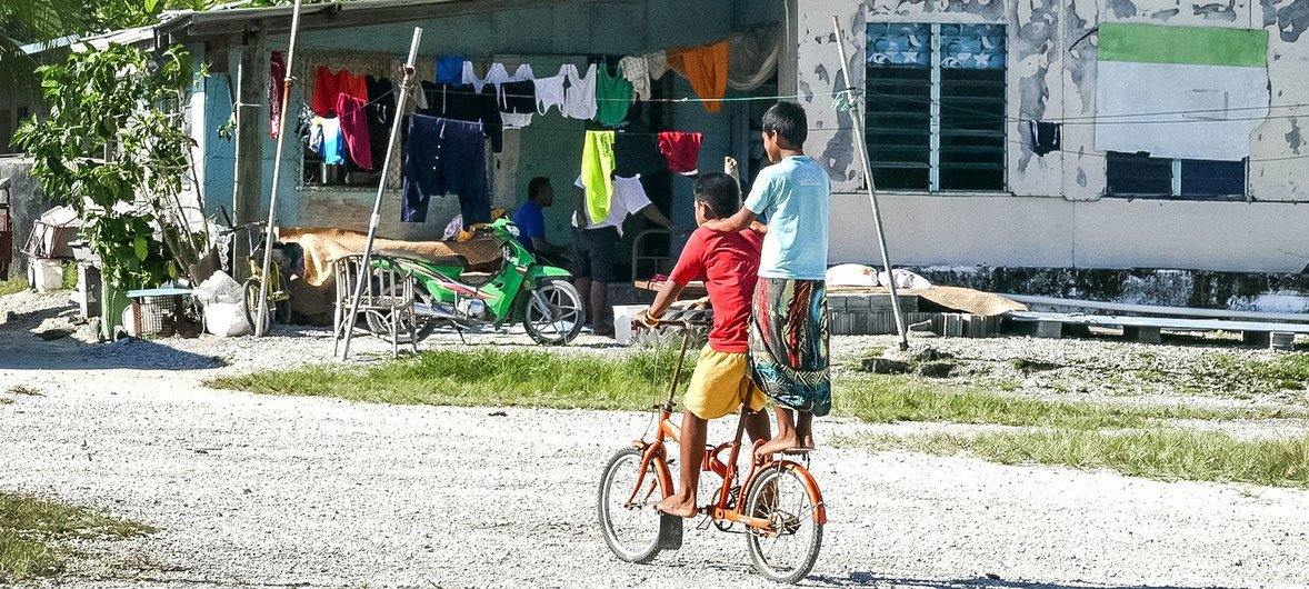 Children riding a bicycle in Tuvalu.