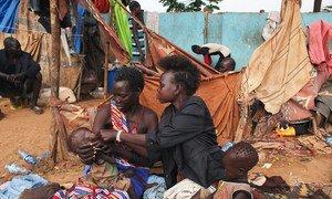 Gemelos en Sudán del Sur que sufren de malnutrición son alimentados por su madre y su tía.