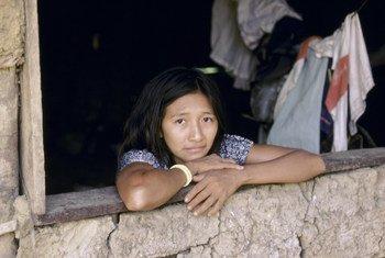 امرأة من حي سكاني لذي الدخل المنخفض في البرازيل تطل من نافذة بيتها.