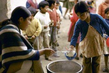 Crianças fazem fila para uma refeição diária em área carente do Equador.