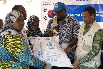Wakuu wa wakimbizi na mwakilishi wa UNHCR wakipokea mgao wa mchele kutoka Korea, Nakivale, Uganda.