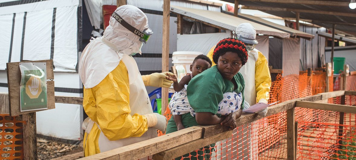A health worker checks a child potentially infected with Ebola being carried on the back of a caregiver at the Ebola Treatment Centre of Beni, North-Kivu province, Democratic Republic of Congo. (24 March 2019)