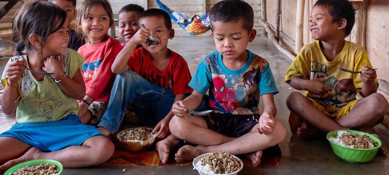 在老挝一所学校的学前班上,孩子们在午休期间吃营养餐。