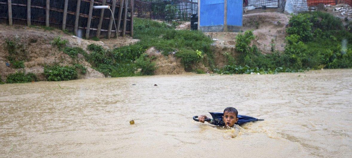 बांग्लादेश में भारी बारिश के बाद उफ़नती नदी को पार करता एक बच्चा.