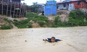 A young boy in Bangladesh navigates a river swollen from days of monsoon rain. He is collecting plastic bottles washed into the river to sell to recyclers to help his family purchase food. (July 2019)