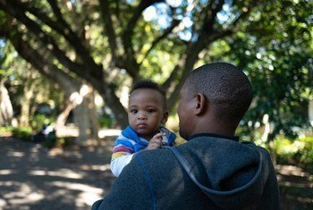 A father holds his son, on a street near his office at the Department of Health in central Cape Town, South Africa. He participated in a UNICEF-supported program that promotes men's involvement as equitable caregivers.
