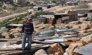 A little boy stands on the remains of his family's demolished  home in the West Bank. (file photo)