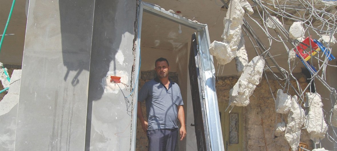 A man stands in what remains of his house in the West Bank after its demolition by the Israeli authorities in September 2018.