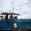 लीबिया के बेनगाज़ी बंदरगाह पर अंतरराष्ट्रीय प्रवासी संगठन के एक जहाज़ से सामान उतारते हुए अन्य देशों के नागरिक. (2011)