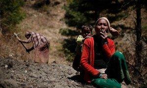 एक महिला खेत में सुस्ताने के दौरान धूम्रपान करते हुए जबकि उसका बच्चा उसके पीछे ही मौजूद है.