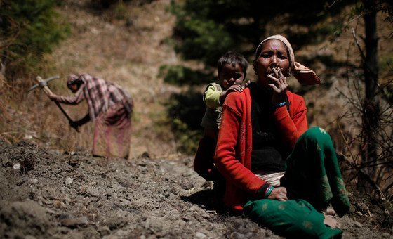 A woman, her child behind her, pauses in the field to smoke a cigarette in Sawa Khola Village, Mugu District.