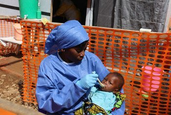 An Ebola health worker in protective gear feeds a baby at an Ebola treatment centre in North Kivu, Democratic Republic of the Congo. (30 January 2019)
