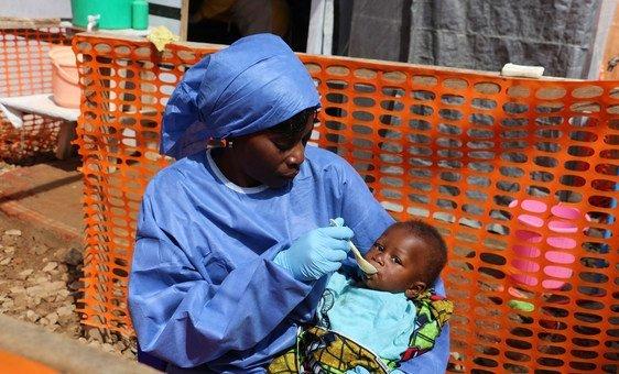 Uma profissional de saúde no combate ao ebola alimenta um bebê em um centro de tratamento em Kivu do Norte, República Democrática do Congo.