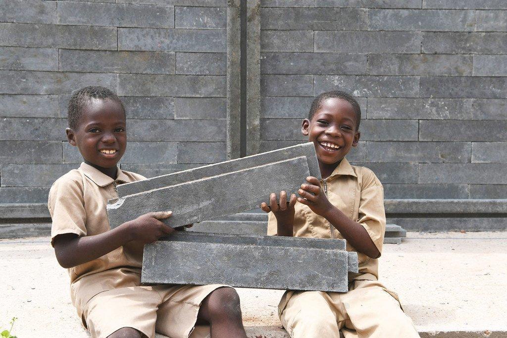 Wanafunzi wakiwa na furaha kwamba darasa  mpya inajengwa shuleni mwao Sakassou mji wa kati wa Côte d'Ivoire kwa kutumia matofali yatoakanyo na taka za plastiki.