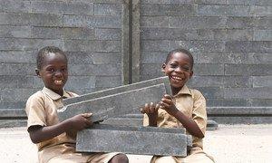 Niños felices porque su nueva aula de clase está siendo construida con ladrillos de plástico en Côte d'Ivoire.