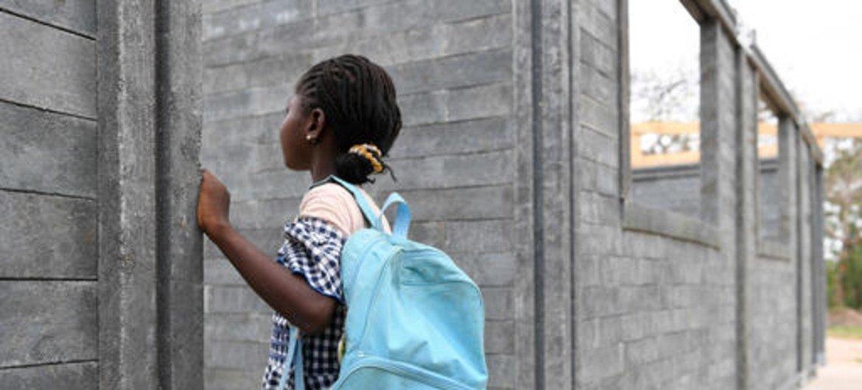 mwanafunzi akiangalia a darasa  mpya linalojengwa shuleni mwao Sakassou mji wa kati wa Côte d'Ivoire kwa kutumia matofali yatoakanyo na taka za plastiki.