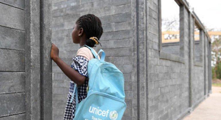 Una niña aprecia su nuevo salón de clase construido con ladrillos de plástico.